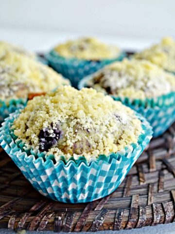 Blueberry Muffins with Streussel Topping on brown bread board from Walking on Sunshine Recipes