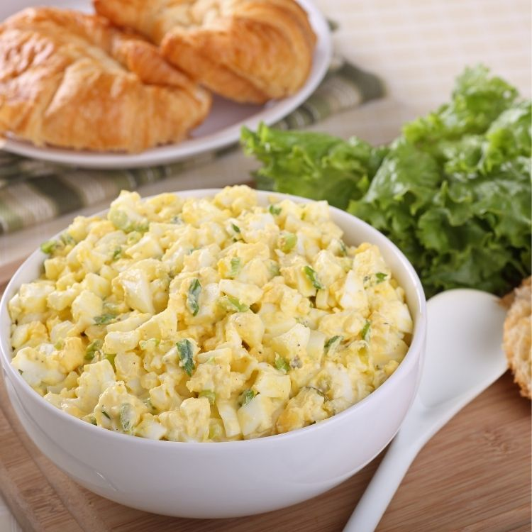 Egg Salad with Leftover Easter Eggs in white bowl with croissants and lettuce.