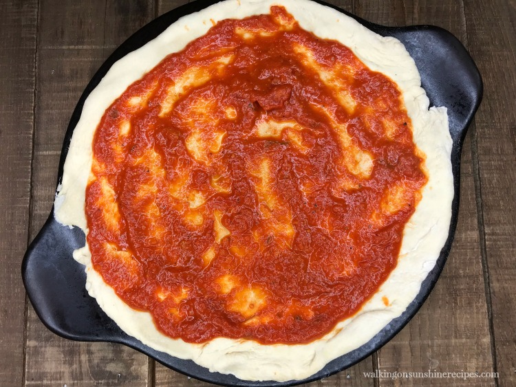 Spread marinara sauce on pizza dough for Homemade Beer Dough Pizza from Walking on Sunshine Recipes