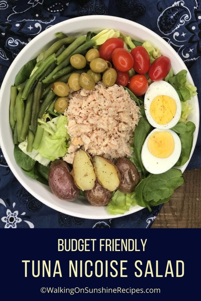 Tuna salad on white plate with eggs, green beans, tomatoes, potatoes and olives.