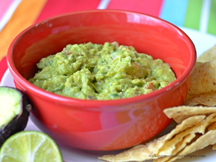 Homemade Guacamole in red bowl with limes on white plate