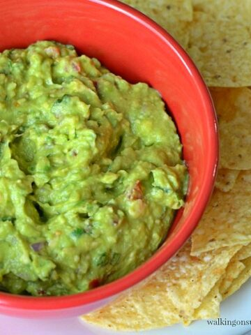 Homemade Guacamole in red bowl with chips from Walking on Sunshine Recipes