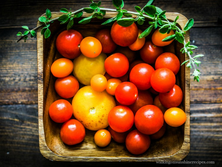 Tomatoes in Wooden Basket with sprig of herbs on top from Walking on Sunshine Recipes
