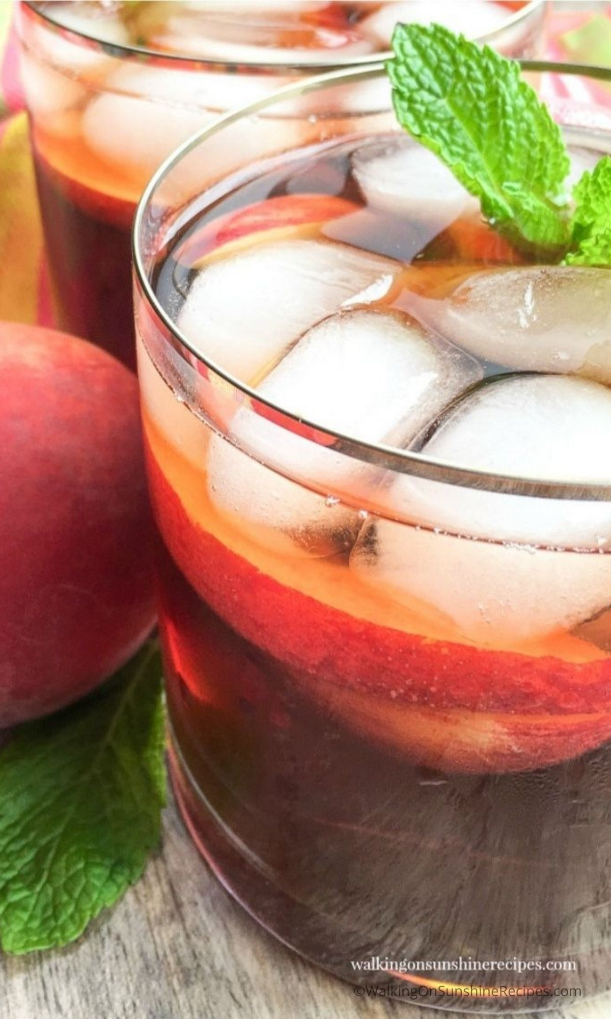 glass with peach tea, ice and sprig of mint.
