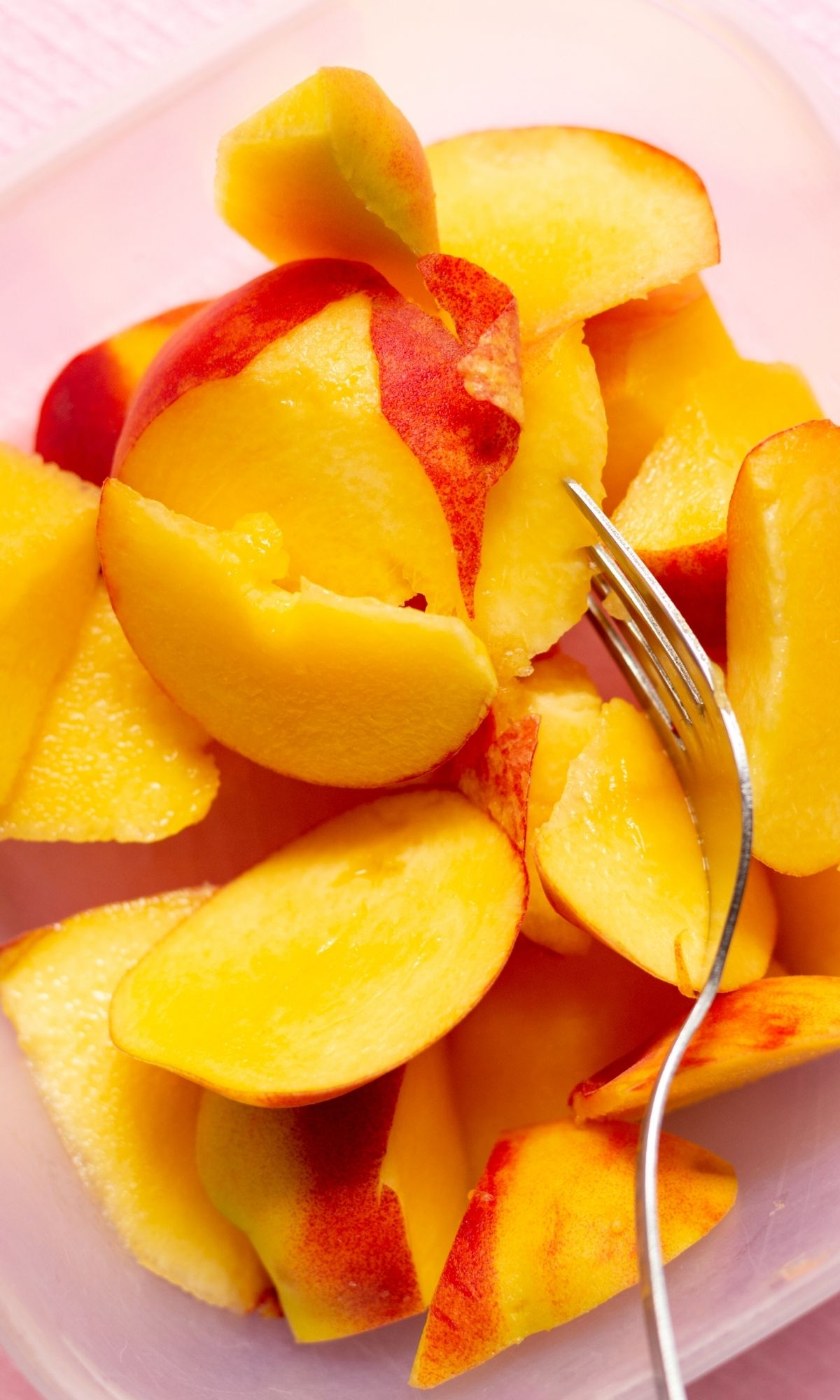 Sliced peaches with fork.