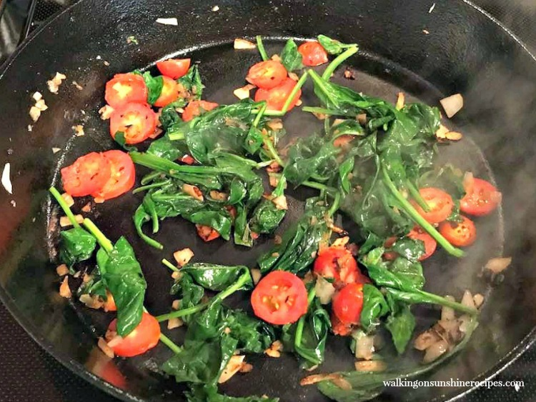 Saute spinach with onions and tomatoes.