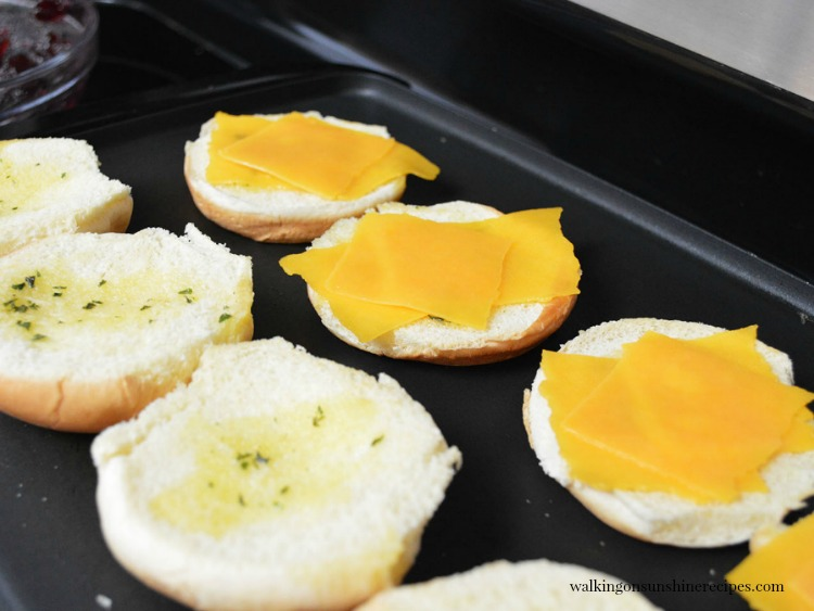 Add sliced cheddar cheese to rolls on top of grilled rolls.