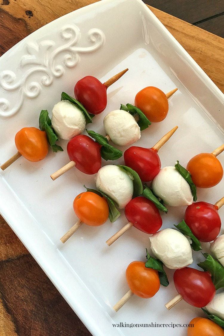 Arrange the cherry tomatoes, basil leaves and mozzarella balls on a short bamboo skewer.