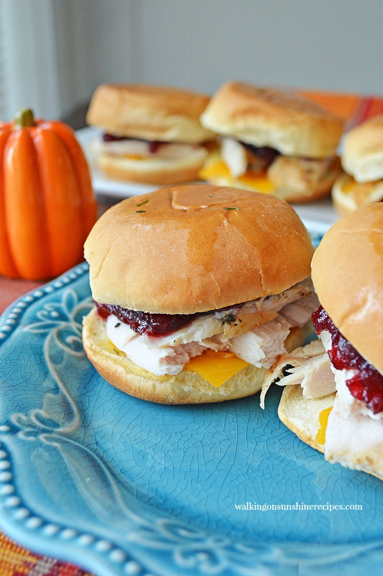 Leftover Turkey Slider Sandwiches on blue plate with cranberry sauce and cheddar cheese.