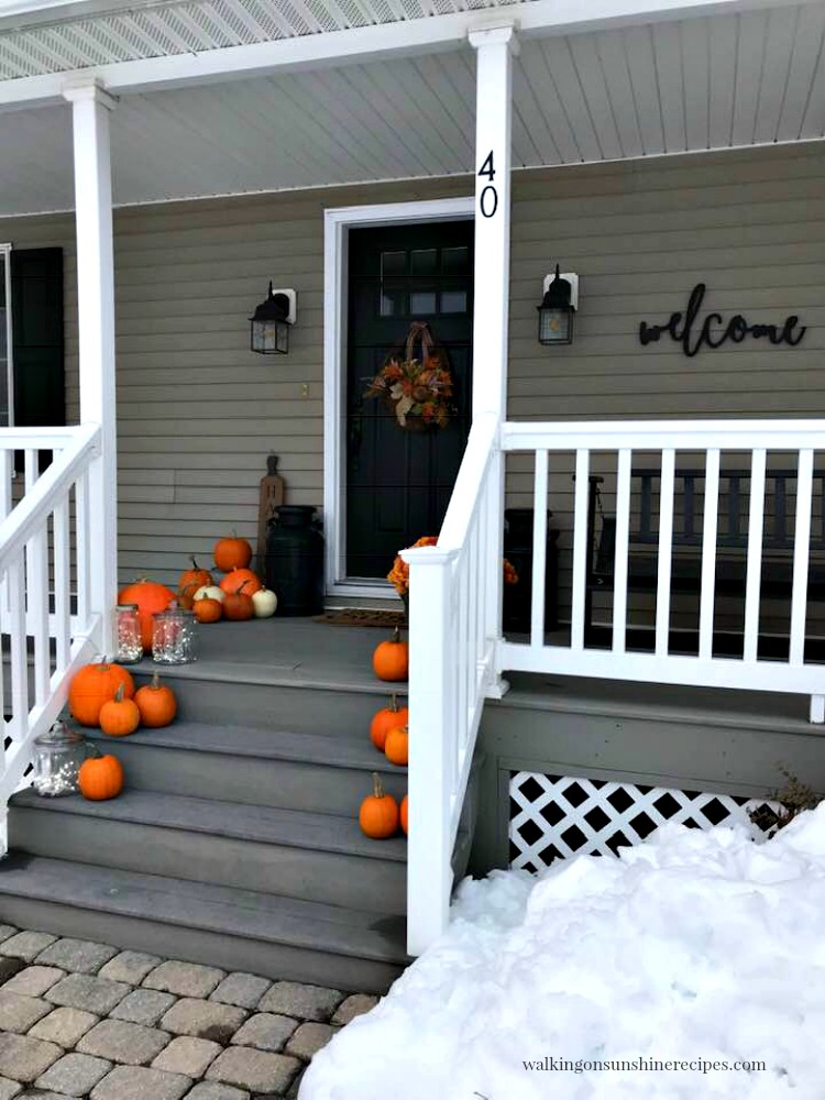 Snow surrounding our front porch with pumpkins and twinkle lights.