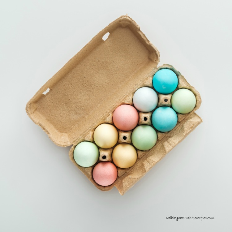 Pastel colored naturally dyed Easter eggs in carton.