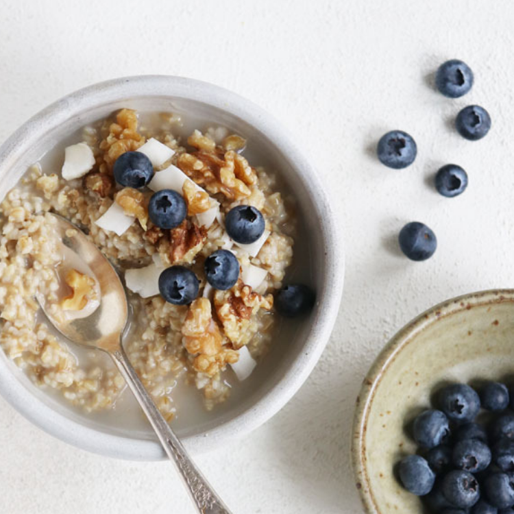 A bowl of oatmeal with blueberries and walnuts.