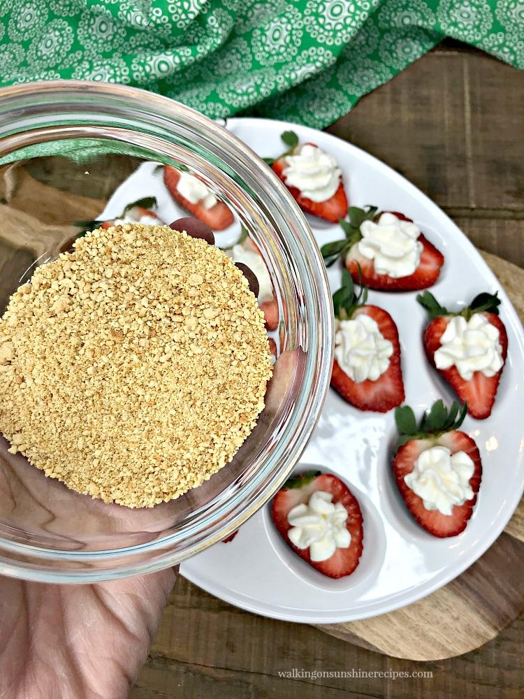 Add crushed graham crackers to Cheesecake Stuffed Strawberries