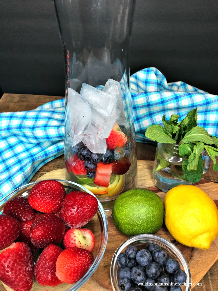 Add ice to infuser bottle with lemons, limes, strawberries and blueberries.