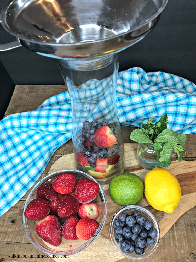 Adding berries and strawberries to glass infuser pitcher.
