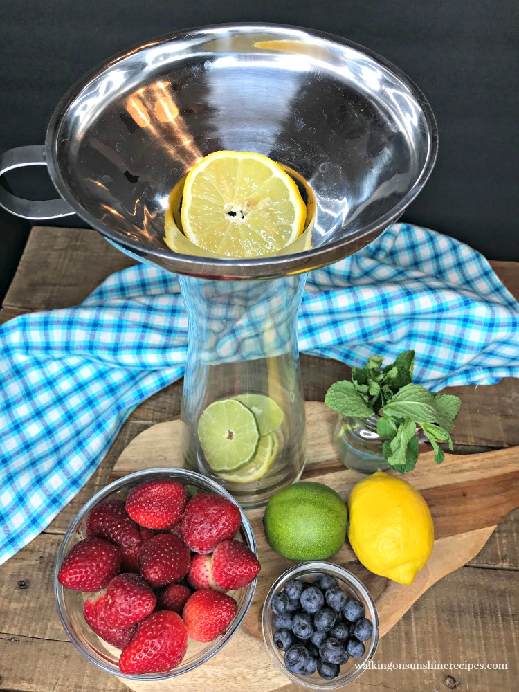 Adding lemons and limes to glass infuser pitcher.