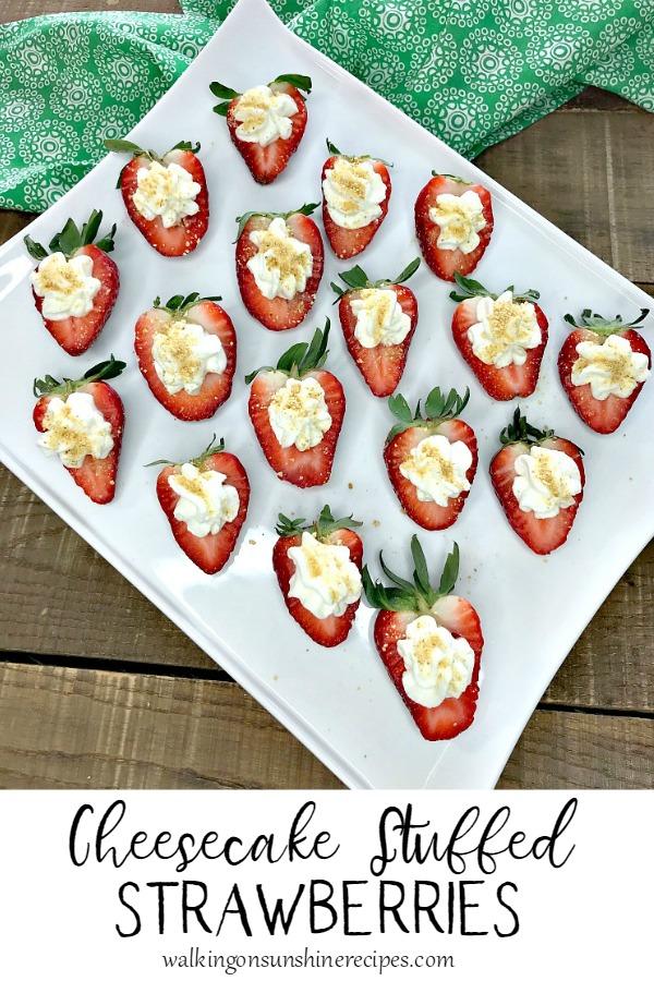 Cheesecake Stuffed Strawberries on white platter with green dish towel.