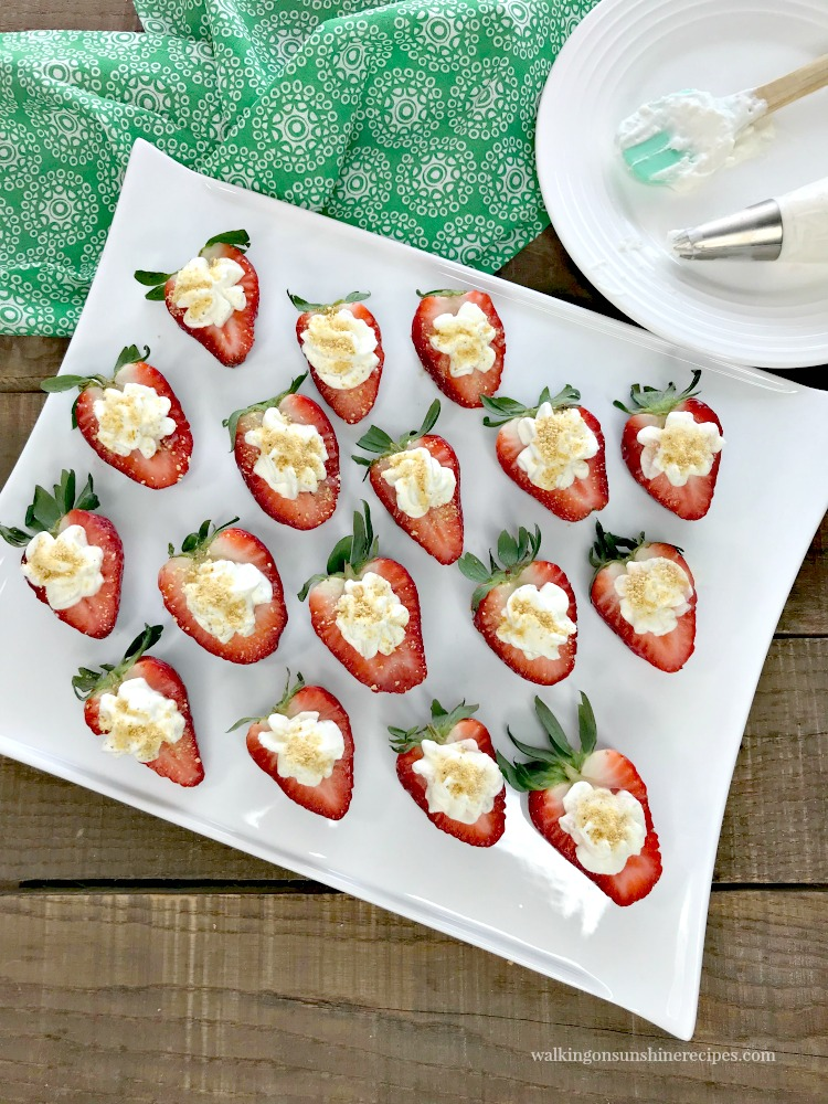 Cheesecake Stuffed Strawberries on white tray with icing bag on plate