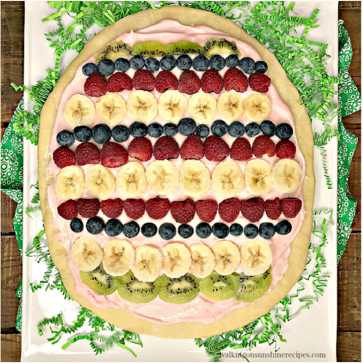 Egg shaped fruit pizza decorated with fresh fruit and tinted pink cream cheese frosting.