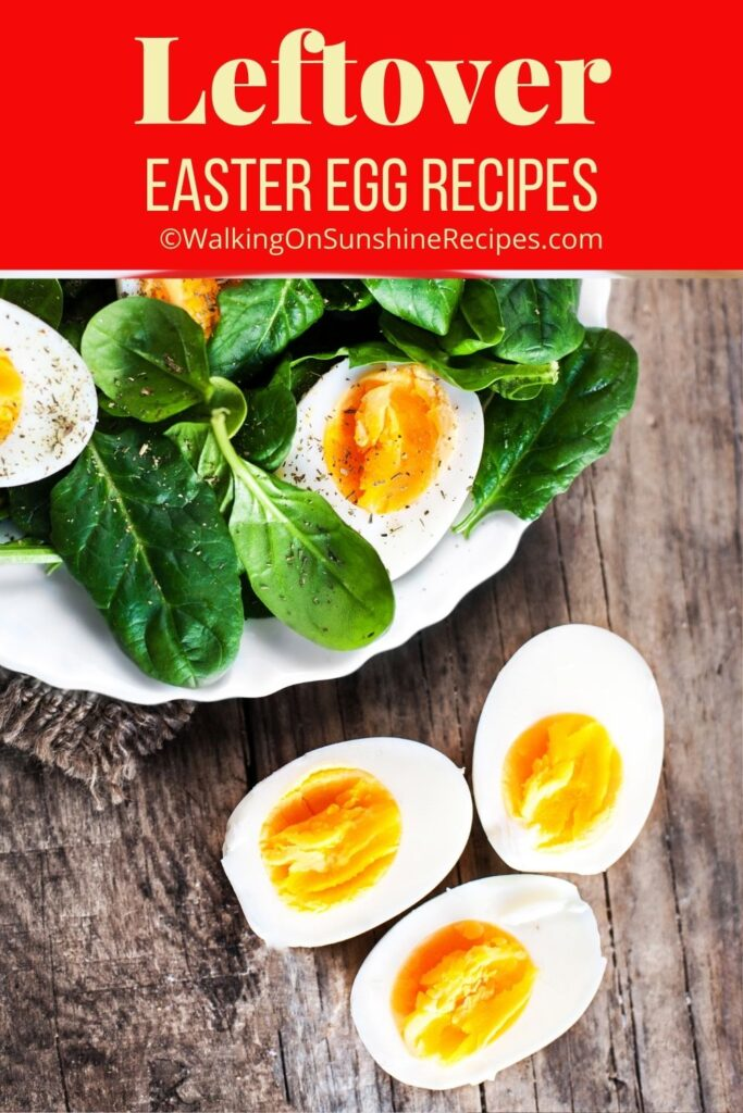 hard boiled eggs sliced on top of fresh spinach leaves.