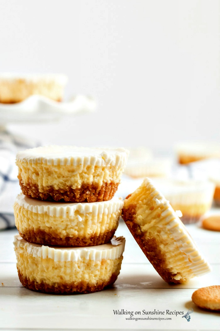 Cheesecake Cupcakes stacked on top of each other on wooden board.