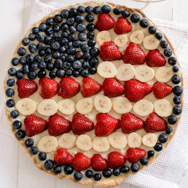 round flag fruit pizza with blueberries, strawberries and bananas.