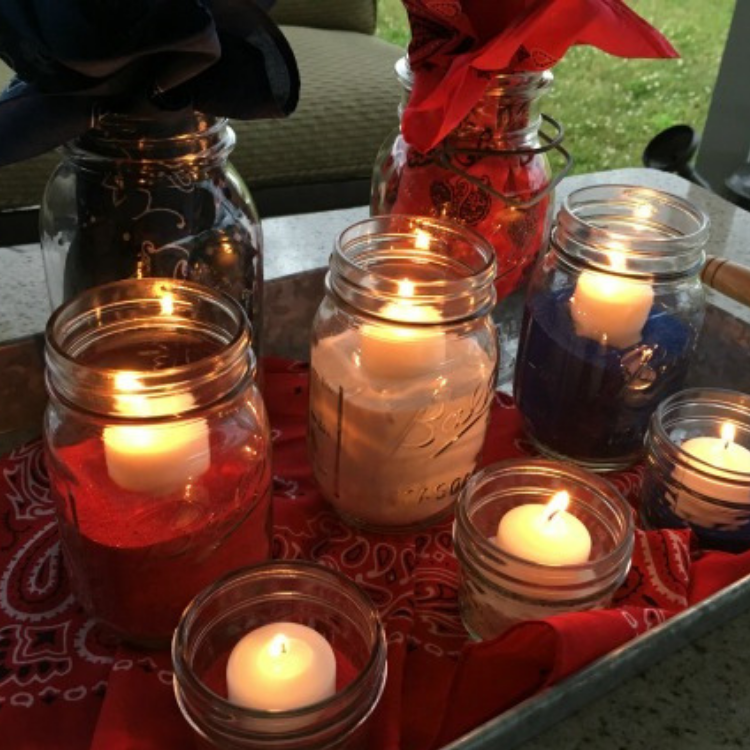 red, white and blue candles in mason jars.