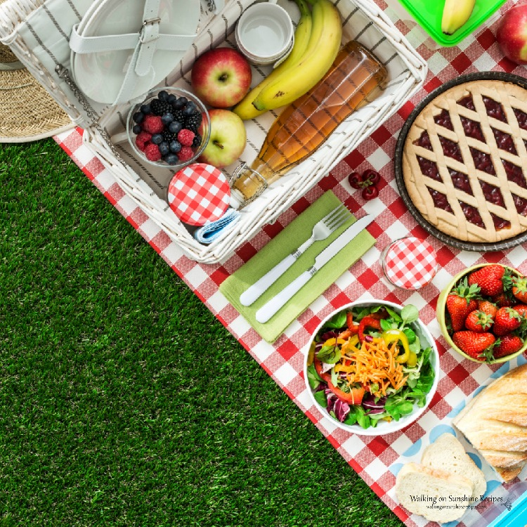 Picnic basket with food on picnic table
