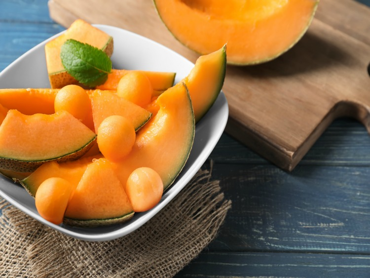 cantaloupe in white bowl and on cutting board.