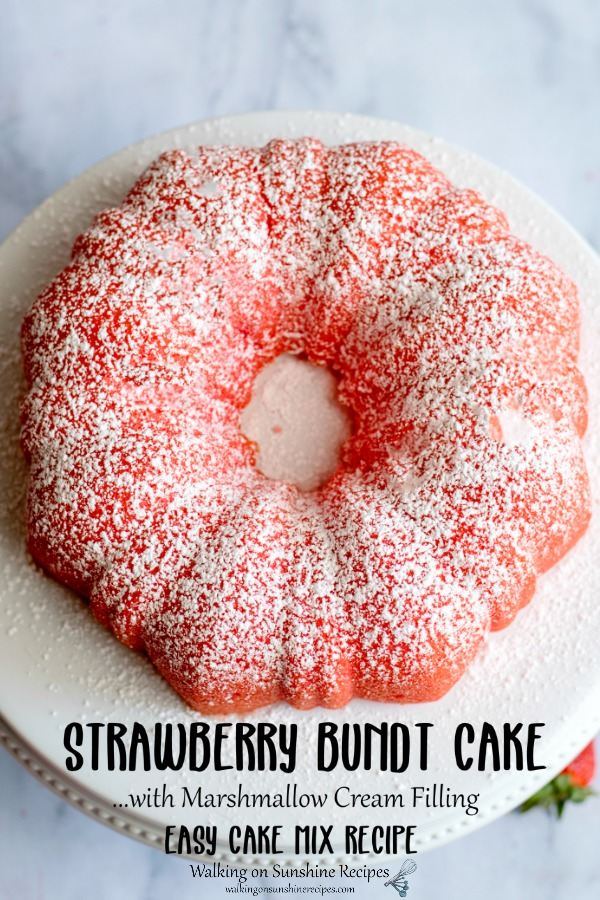 Strawberry bundt cake with powdered sugar on white cake stand.