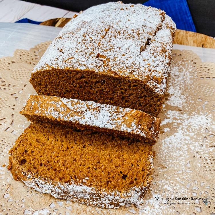Slice pumpkin bread with powdered sugar on cutting board.