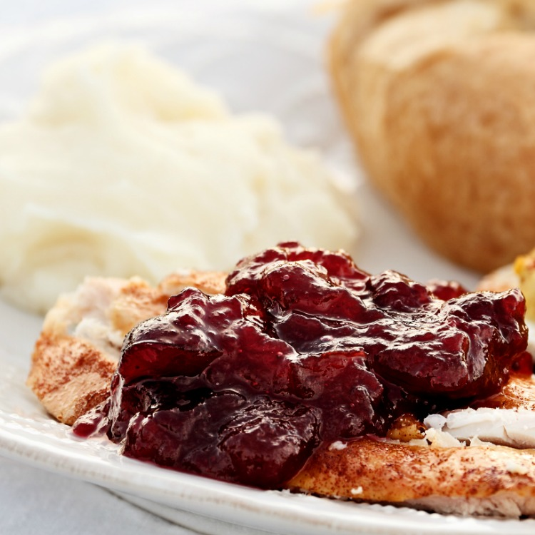 Homemade Cranberry Sauce served over slice Turkey