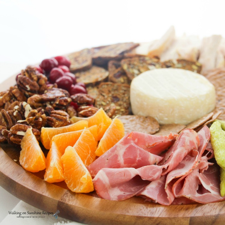 Ham, oranges, nuts, crackers and Brie Cheese on Cheese Board