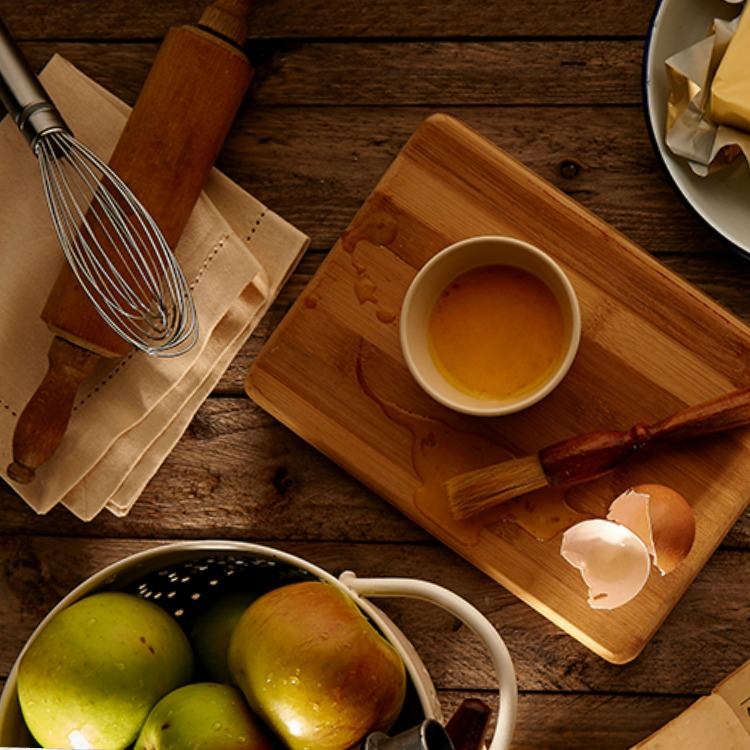 Cutting board with eggs, apples and butter.