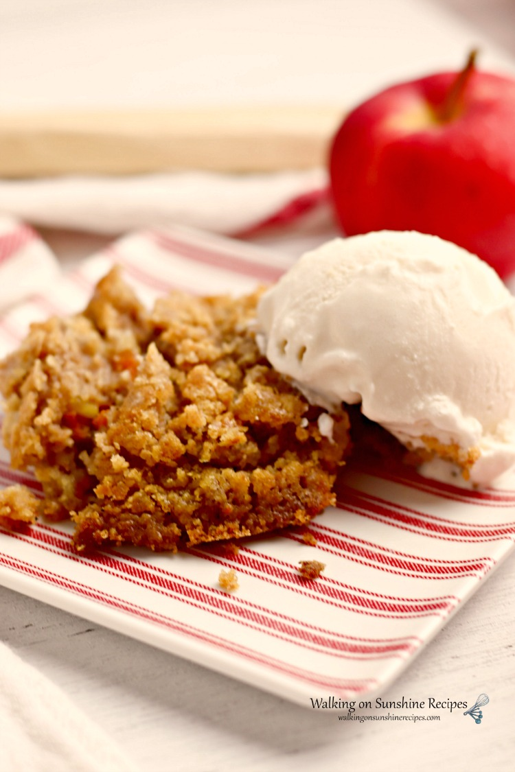 Pumpkin Apple Dump Cake on red and white plate with vanilla ice cream with red apple in background.