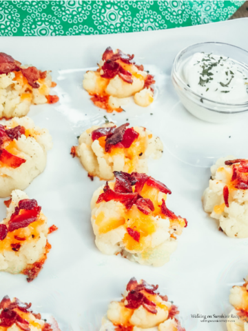 Loaded Cauliflower Bites on white plate with sour cream