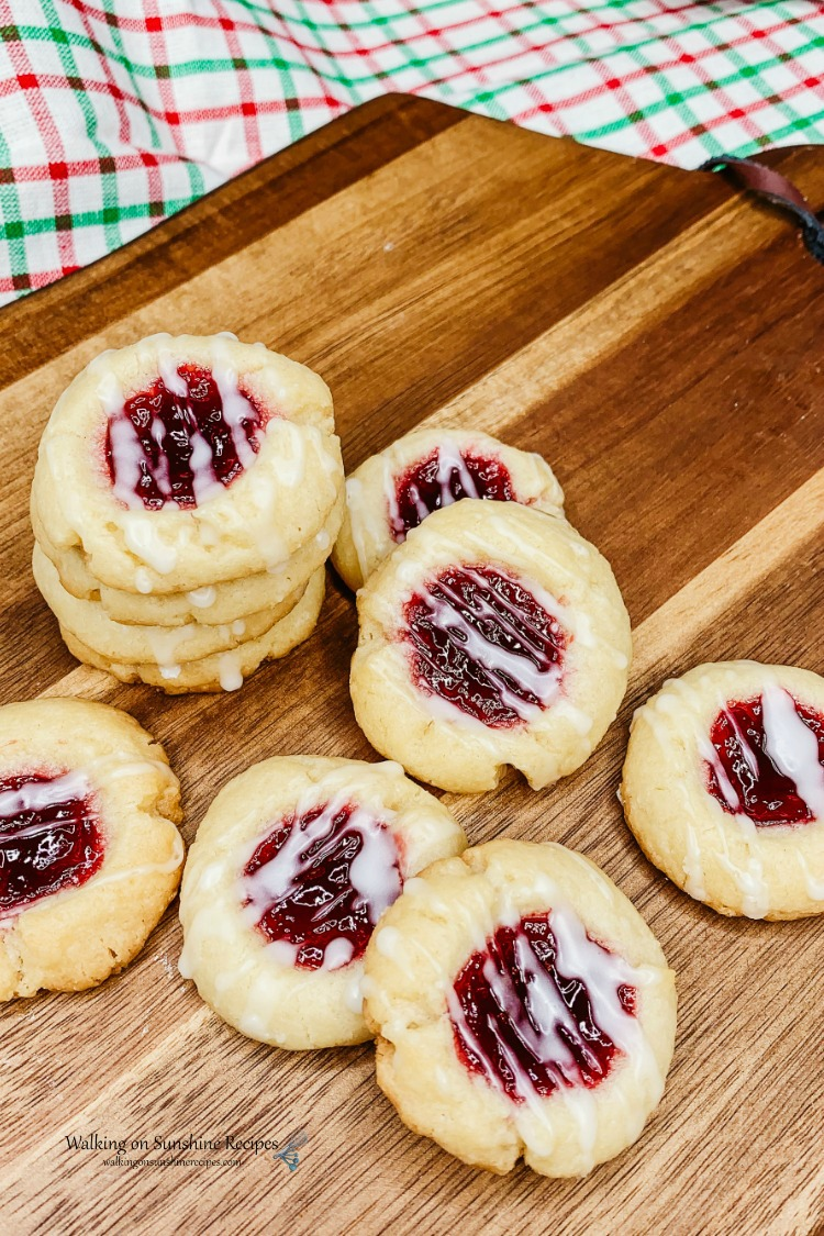 Closeup of stacked raspberry shortbread thumbprint cookies with sugary glaze on cutting board.