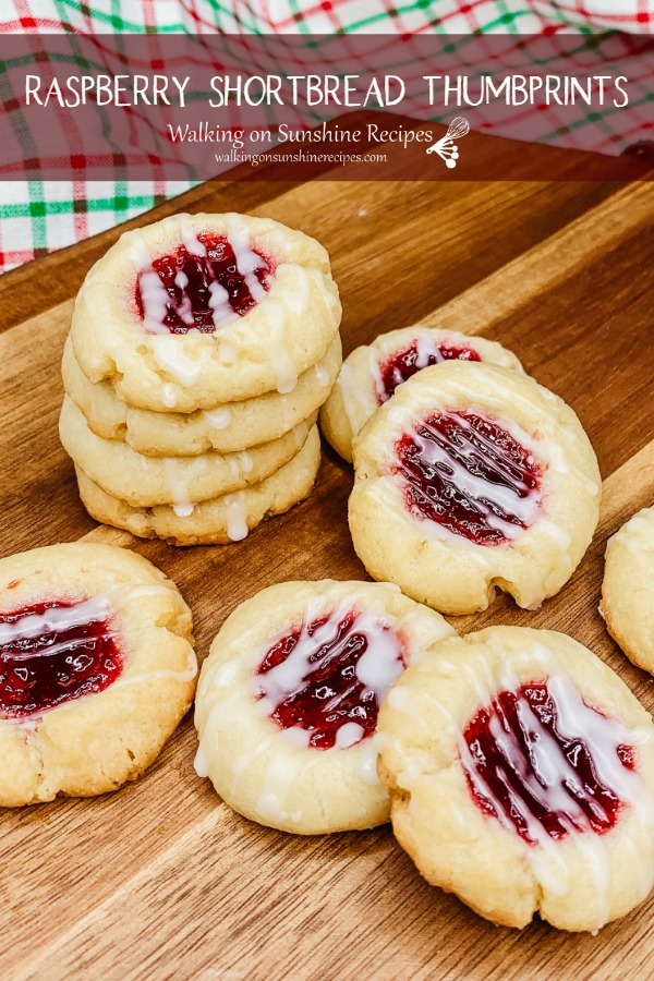 Stacked raspberry shortbread thumbprint cookies on wooden board