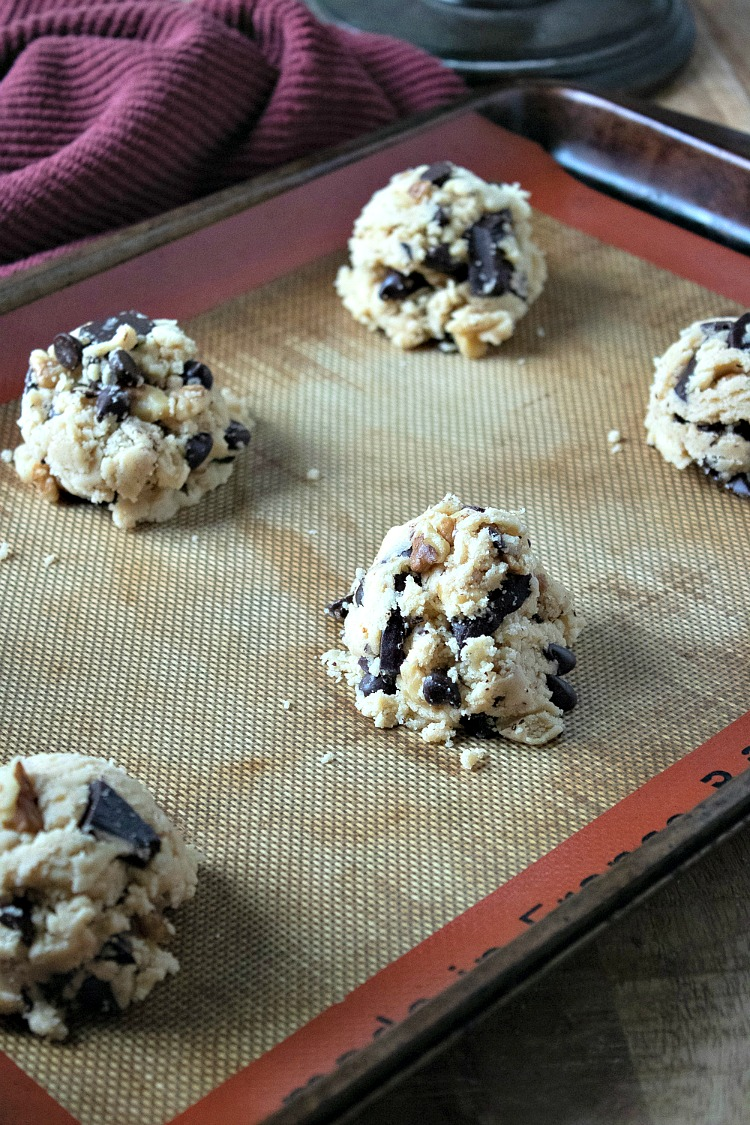 Scoops of Walnut Chocolate Chunk Cookies on baking tray before baking