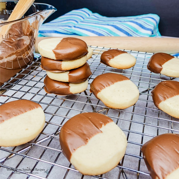 Slice and Bake Shortbread Cookies dipped in melted chocolate stacked on wire baking rack.