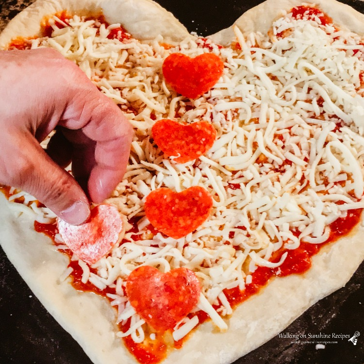 Adding heart shaped pepperoni slices to the top of homemade pizza made with marinara sauce and mozzarella cheese.