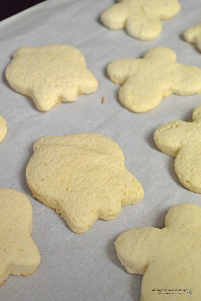 Baked sugar cookies on baking tray lined with parchment paper.