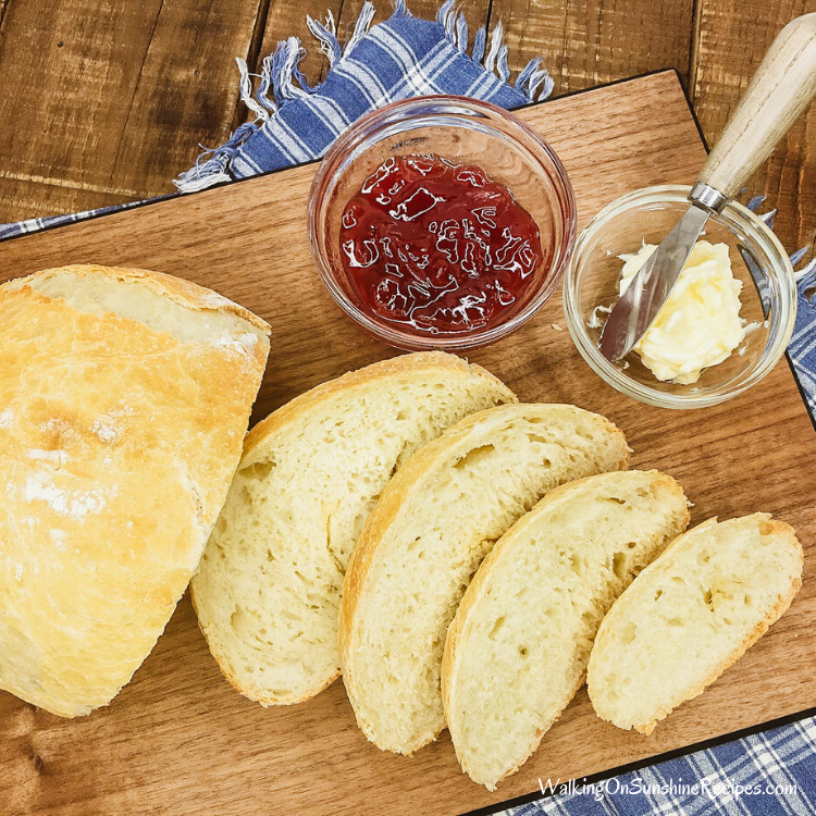 Sliced no knead bread on cutting board with butter and jam.