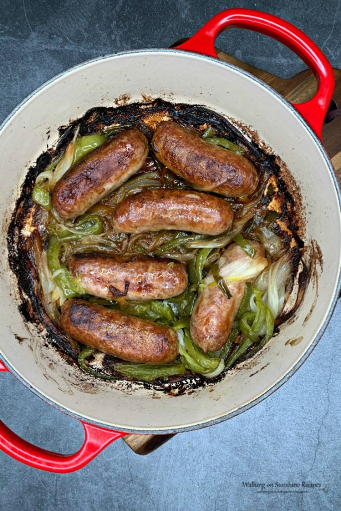 Sausage and Peppers in red casserole dish on cutting board from WOS