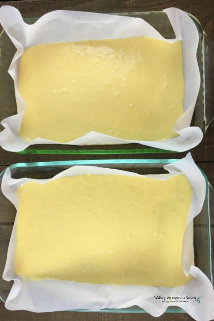Vanilla cake batter divided between two baking pans.