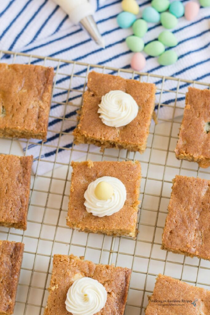 Adding homemade cream cheese frosting to the tops of Candy Cookie Bars.