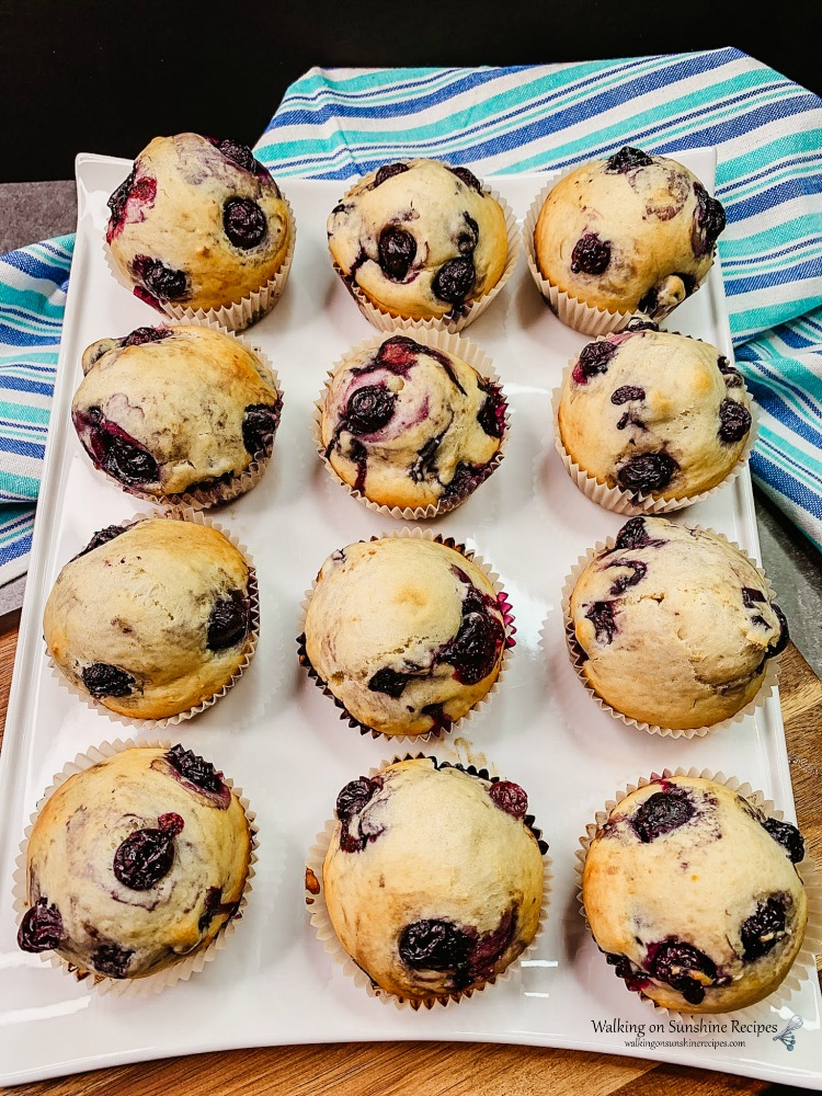 Blueberry Muffins on white tray with blue striped dish towel from Walking on Sunshine Recipes
