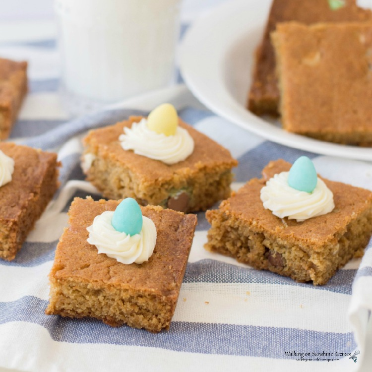 Candy Cookie Bars on plate with homemade cream cheese frosting swirls on top.