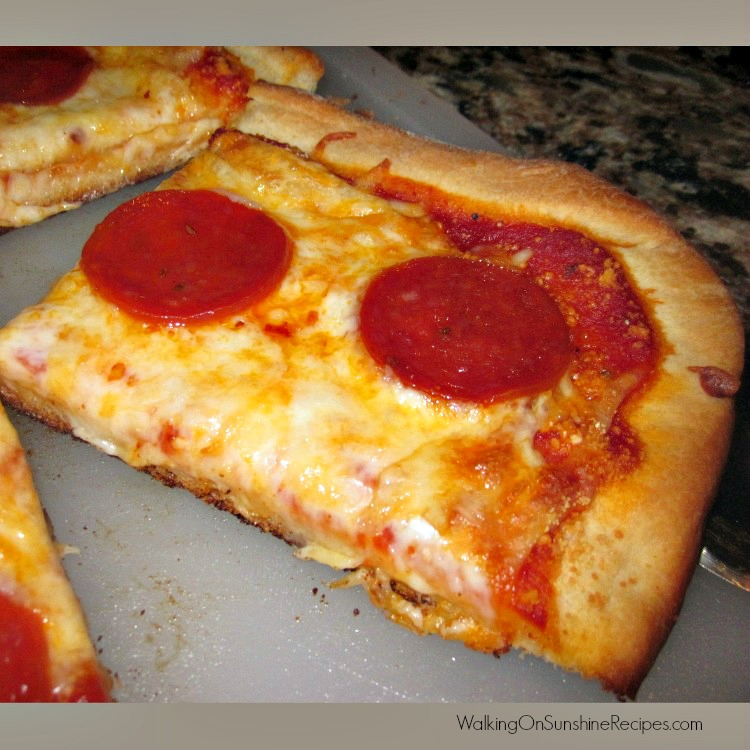 One square slice of homemade pizza dough with sauce, cheese and pepperoni.