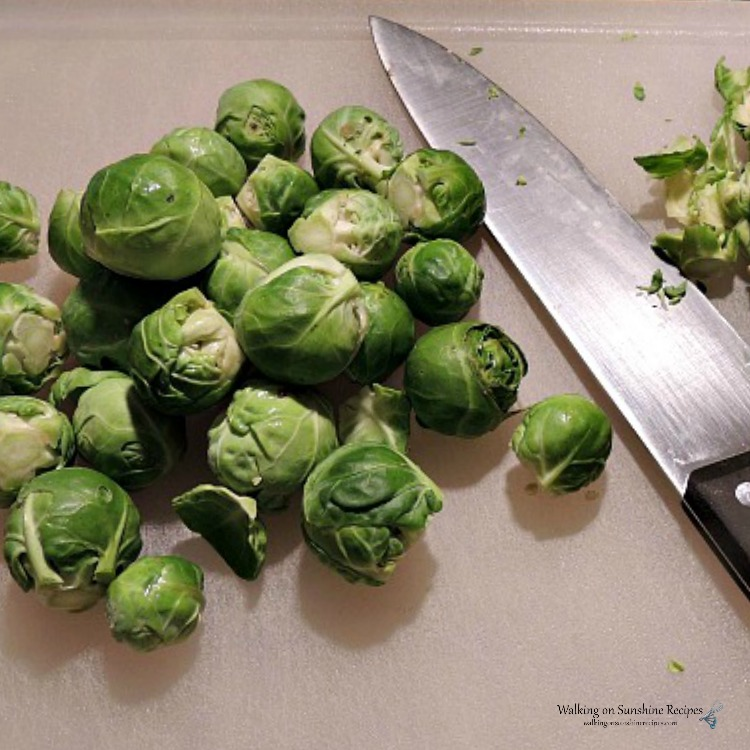 Trim Brussels Sprouts on cutting board with sharp knife